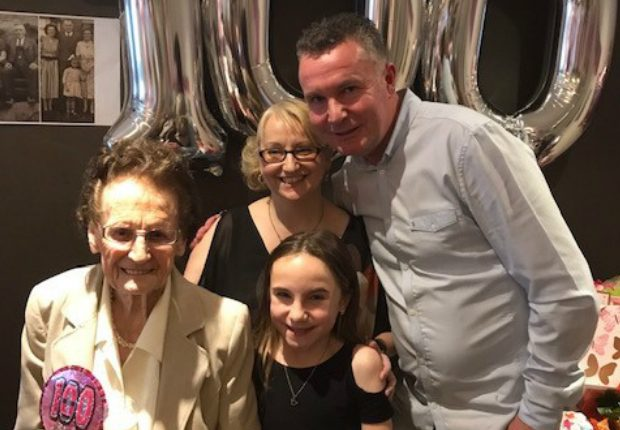 Two adults and a child with someone celebrating their 100th birthday.