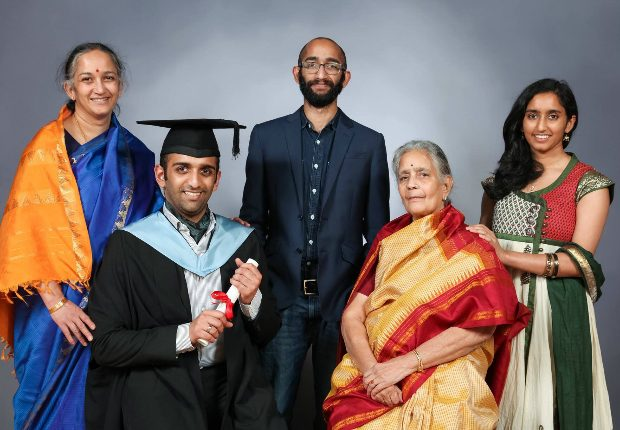 Vishal sitting with 4 of his family members, dressed up for his graduation and holding his degree scroll.