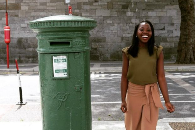 Racheal smiling and standing next to a post box.
